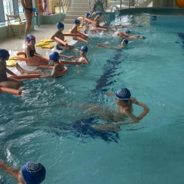grupa dzieci uczy się pływać w basenie