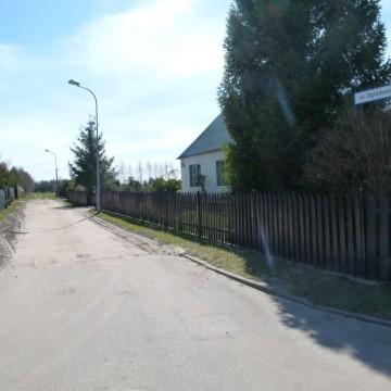 droga asfaltowa obok posesji prywatnej z domem mieszkalnym